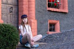 Ein Mädchen sitzt nahe einem schönen Haus und Lächeln süß stockfotografie
