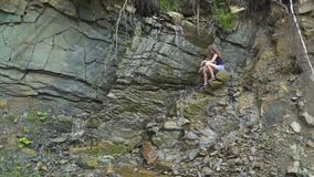 Ein Mädchen spielt einen Wasserfall stock video