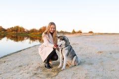 Ein Mädchen spielt mit einem Hund auf der Flussbank Schöner heiserer Hund Der Fluss Herbst stockfotos