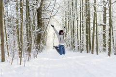 Ein Mädchen springt im Wald oben Viel Schnee stockfotografie