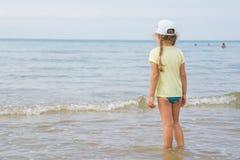 Ein Mädchen steht auf dem Ufer und untersucht den Abstand zum Meer Stockfotografie