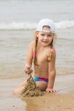 Ein Mädchen steht auf dem Ufer und untersucht den Abstand zum Meer Stockbild