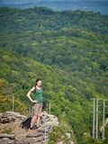 Ein Mädchen steht auf einer Klippe vor dem hintergrund des grünen Waldes stockfotos