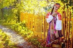 Ein Mädchen steht einen Zaun in einem russischen Kostüm bereit Stockfotografie