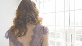Ein Mädchen steht am Fenster und schaut stock footage