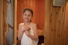 Ein Mädchen steht, lächelnd vor dem Eingang des finnischen sa lizenzfreie stockfotos