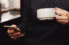 Ein Mädchen trinkt Kaffee und benutzt einen Handy in einem Café stockbilder