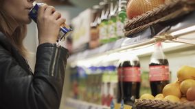 Ein Mädchen trinkt Saft von einem Regal in einem Supermarkt und in den Blättern stock video