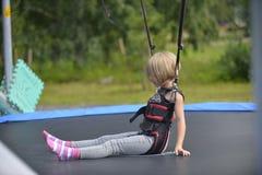 Ein Mädchen tut das Springen auf die springende Anziehungskraft Lizenzfreie Stockbilder