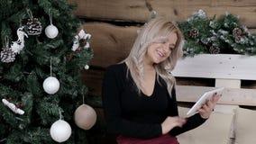 Ein Mädchen tut das Weihnachtseinkaufen im Internet mit einer Tablette stock footage