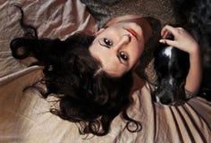 Ein Mädchen und ein Hund, die im Bett liegen Stockfotografie