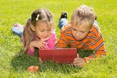 Ein Mädchen und ein Junge mit Tablet-Computer lizenzfreies stockbild