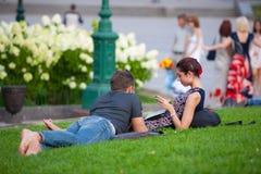 Ein Mädchen und ein junger Mann, die auf dem Rasen stillstehen Stockfoto