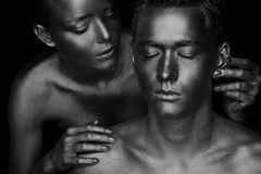 Ein Mädchen und ein Kerl bedeckt in der Goldfarbe Wenn meine Augen geschlossen sind Das Mädchen gelehnt, Schwarzweiss Lizenzfreies Stockfoto