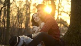Ein Mädchen und ein Kerl stehen im Park still und küssen, das Umarmen und lachen auf dem Sunse stock video footage