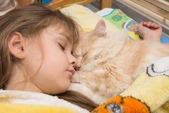 Ein Mädchen und eine Katze schlafen süß im Bett Stockfotografie