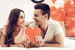 Ein Mädchen-und Guy Kiss Holding Red Heart-Origami stockfotografie