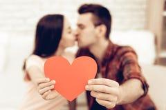 Ein Mädchen-und Guy Kiss Holding Red Heart-Origami lizenzfreie stockfotografie