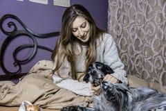 Ein Mädchen und ihr Hund, die im Schlafzimmer aufwachen Stockbilder