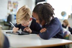Ein Mädchen und ein Junge, der einen Tablet-Computer und einen Griffel in einer Grundschuleklasse nah betrachtet dem Schirm verwe stockfotografie