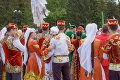 Ein Mädchen und ein Kerl in der tatarischen nationalen Kleidung, die unter einer Menge von Leuten umarmt lizenzfreie stockbilder