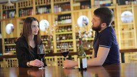 Ein Mädchen und ein Kerl in einem Restaurant teilen mit und trinken Rotwein, einen Rotwein der jungen Paargetränke an einem Tisch stock video footage
