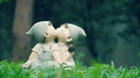 Ein Mädchen und Puppen eines Jungen, küssend und sitzen in der Wiese Stockbild