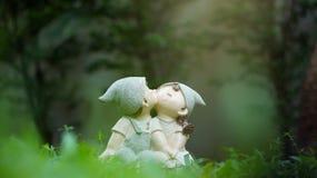 Ein Mädchen und Puppen eines Jungen, küssend und sitzen unter grünem Gras Lizenzfreies Stockfoto