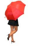 Ein Mädchen unter dem roten Regenschirm Stockfotografie