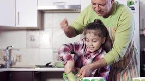Ein Mädchen unter Führung seiner Vatergitterzucchini stock video footage
