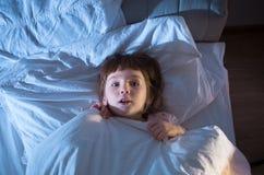 Ein Mädchen von 4 Jahren hat vor dem Lügen im Bett Angst Stockbilder