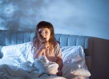 Ein Mädchen von 4 Jahren schreit das Sitzen auf dem Bett in der Nacht Stockfotografie