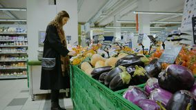Ein Mädchen wählt das Gemüse im Supermarkt in Italien stock footage