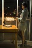 Ein Mädchen, welches das Fenster mit dem menorah feiert Chanukka bereitsteht Stockfoto