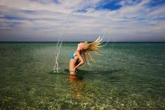 Ein Mädchen, welches das Meerwasser mit ihrem Haar spritzt Stockfotos