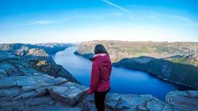 Ein Mädchen, welches die Fjordansicht vor ihr in Norwegen genießt lizenzfreie stockbilder