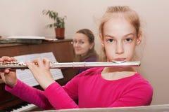 Ein Mädchen, welches die Flöte spielt Stockbild