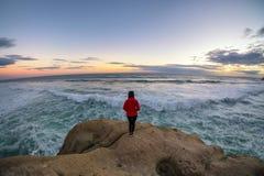 Ein Mädchen, welches die starken Naturgewalten am Rand einer Klippe bewundert lizenzfreie stockfotografie