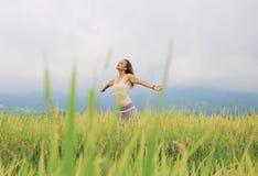 Ein Mädchen, welches tief das Reis-Feld einatmt stockbild
