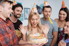 Ein Mädchen wird mit einem Kuchen mit Kerzen für Geburtstag erfreut Sie zeigt den Gästen ihre Freude Stockfotografie