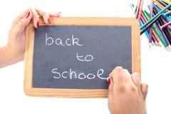 Ein Mädchenschreiben zurück zu Schule auf Tafel Lizenzfreie Stockfotos