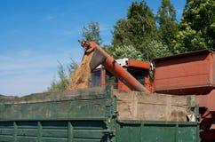 Ein Mähdrescher gießt Korn in einen Kipplaster Stockbilder