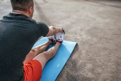 Ein männlicher Athlet, der Gymnastik auf Matte, Muskeln ausdehnend, Ausbildungssommerstadt auf Sportfeld tut Aktives Training stockbild