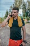 Ein männlicher Athlet hält ein Telefon in seiner Hand, in den Anrufen am Telefon und in den Resten nach einem Training in der Fri lizenzfreie stockbilder