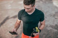 Ein männlicher Athlet hält Telefon in seiner Hand, startet eine Anwendung für Training Im Sommer Ansicht von der Spitze der Schüt stockfotografie