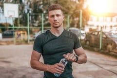 Ein männlicher Athlet, im Sommer auf dem Sportquadrat, in seinen Händen, die eine Flasche Wasser halten Verringern Sie Durst nach stockfoto