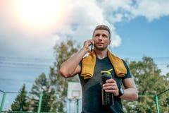 Ein männlicher Athlet, Sommerstadt nach einem Training, Anrufe am Telefon, hält in seiner Hand einen Schüttel-Apparat, eine Flasc lizenzfreie stockbilder