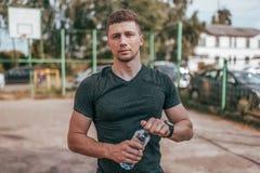 Ein männlicher Athlet steht im Sommer auf Sportplatz in der Stadt In seiner Hand eine Flasche Wasser, stehend nach Übung still stockbilder
