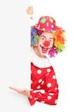 Ein männlicher Clown, der auf eine Leerplatte gestikuliert Lizenzfreies Stockfoto