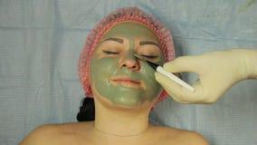 Ein männlicher Cosmetologist, der Handschuhe trägt, setzt eine Schlammmaske auf das Gesicht eines client's Kunden mit einer spe stock video